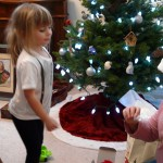 Trinity and Ella examine a feather in front of the tree